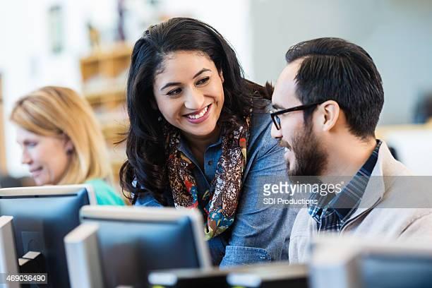 Freundliche Hispanic Frau mit computer mit college classmate