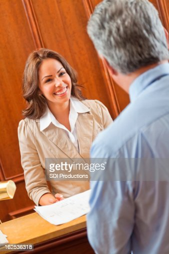 Friendly hotel manager greeting guest in lobby at check-in desk