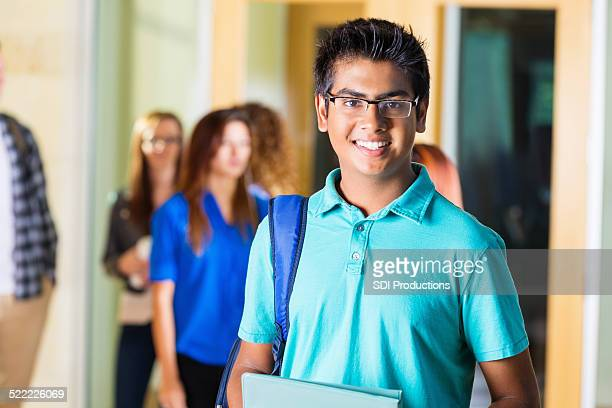 Friendly Indian high school student smiling in hallway
