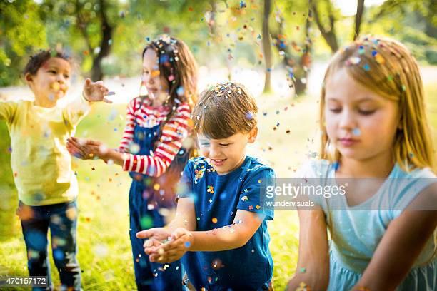 Freundliche Kinder, die Spaß mit Konfetti im park