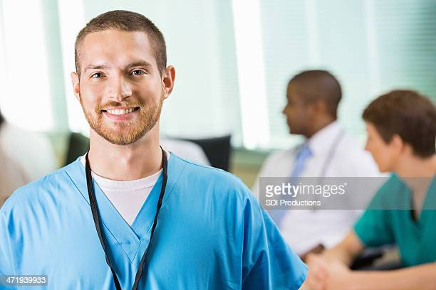 Friendly male nurse or physician in hospital staff meeting