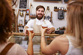 Friendly young man with beard standing behind the cafe counter and serving coffee for two women. Young man working in restaurant, helping customer with coffee.