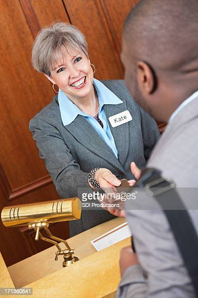 Friendly manager smiles and helps guest at nice hotel