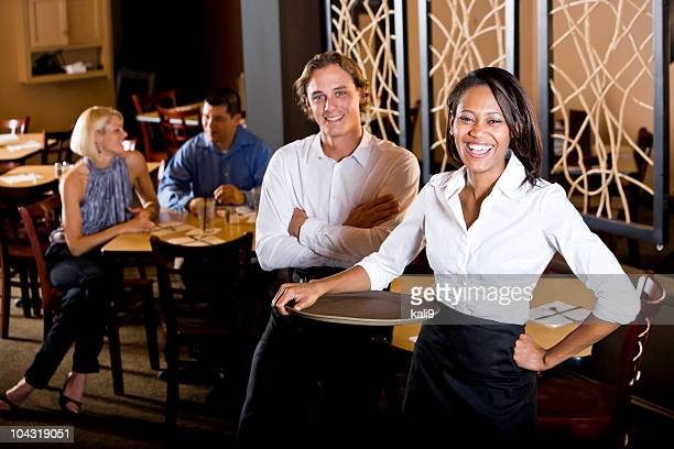 Friendly multiracial restaurant waiters, customers in background at table