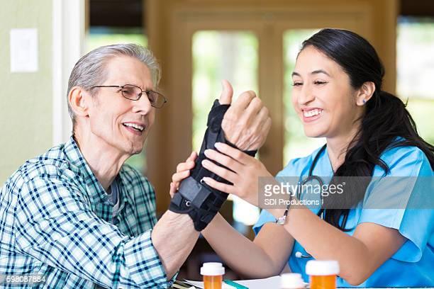 Friendly nurse examines senior patient's wrist