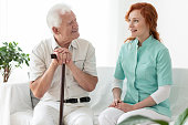 Friendly nurse talking with smiling elderly man with walking stick