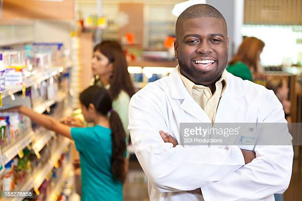 Friendly pharmacist in front of customers at his pharmacy