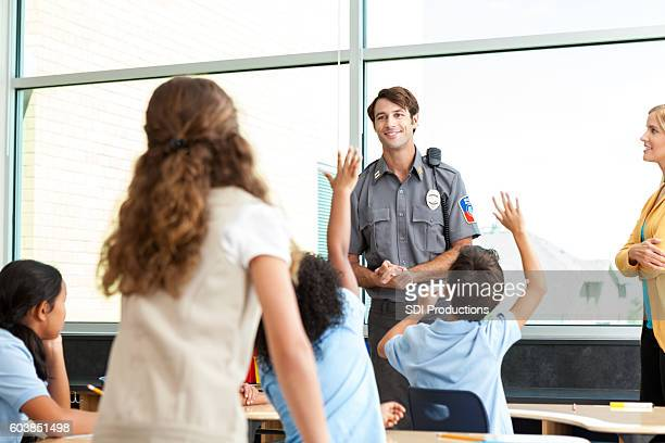 Friendly police officer addresses class of students