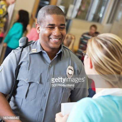 Friendly police officer talking with school teacher after safety demonstration