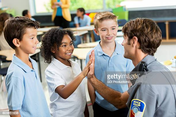 Friendly policeman gives high five to excited student