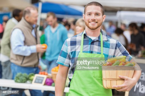 Friendly produce vendor smiling at outdoor farmers market booth
