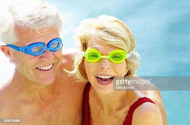 Friendly retired couple wearing swimming goggles