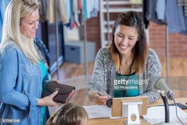 Friendly sales clerk scans customer's credit card