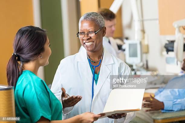 Sympathique médecin senior féminin patient d'hôpital parler avec infirmier tableau
