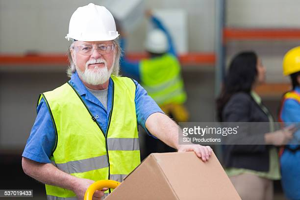 Friendly senior warehouse employee moving boxes during shift