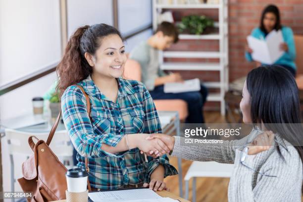 Friendly student greets a friend in the student center