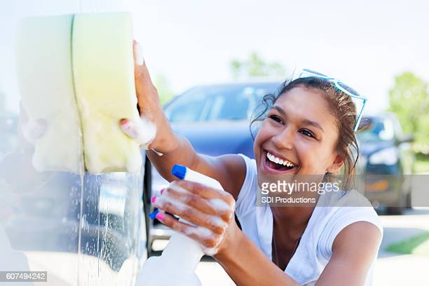 Friendly teenager enjoys washing car during fundraiser