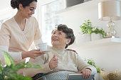 Friendly volunteer giving cup of tea to happy senior woman in nursing house