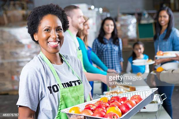 Friendly volunteer serving fresh fruit at community soup kitchen