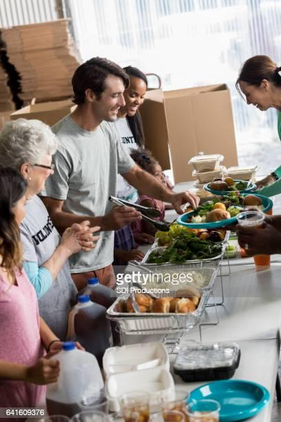 Friendly volunteers serve people in soup kitchen