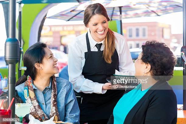 Les Serveuse livraison de repas pour les clients du restaurant en plein air