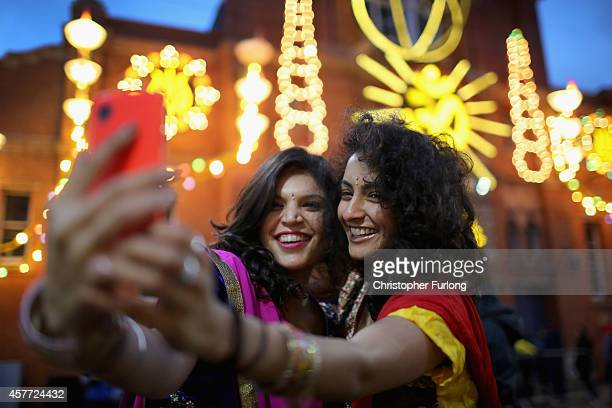 Friends Aanka Batta and Kelly Vaduka take a selfi in front of illuminations as they celebrate the Hindu festival of Diwali on October 23 2014 in...