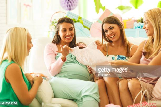 Friends admiring baby clothing at baby shower