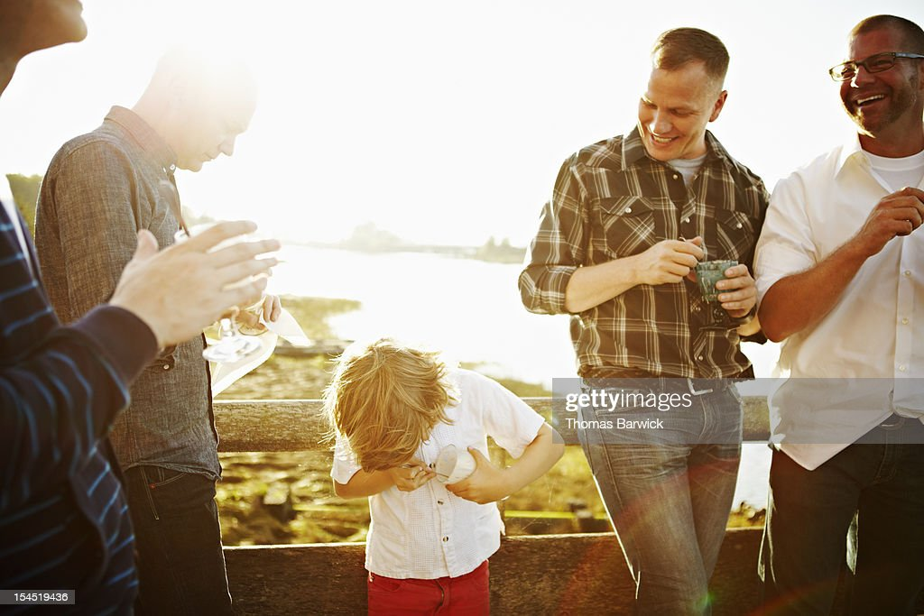 Friends and family eating dessert on dock : Stock Photo