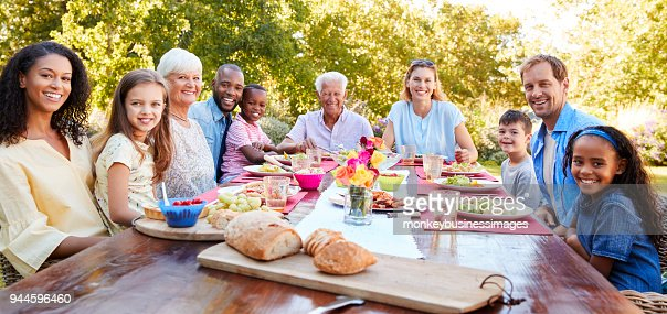 Friends and family having lunch in garden, looking to camera : Foto stock