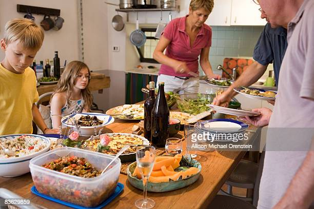 Friends and family in kitchen serving food