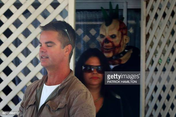 Friends and family members including one wearing a mask of Schapelle Corby await Corby's return to her mother's home in Loganlea on May 28 2017...