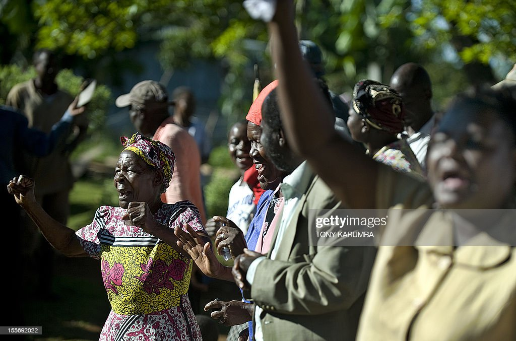 Friends and family members of Sarah Obama (L), step-grandmother of USA's President-elect, Barack Obama sings and dances at her homestead in the hamlet of Kogelo in western Kenya following media-announcements of Barack's apparent electoral victory early on November 7, 2012. President Barack Obama swept to a emphatic re-election win over Mitt Romney on November 6, 2012 forging new history by transcending a dragging economy and the stifling unemployment which haunted his first term. AFP PHOTO / Tony KARUMBA