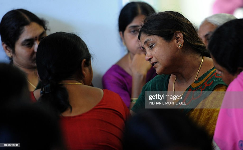 Friends and family members sit around the grieving relative (2R) of a bomb blast victim at the Yashoda Hospital in Hyderabad on February 22, 2013. Indian police revealed Friday they had been warned of a possible attack by Islamist militants in a bustling shopping area of Hyderabad where twin bombings killed at least 14 people and wounded scores. AFP PHOTO/Indranil MUKHERJEE