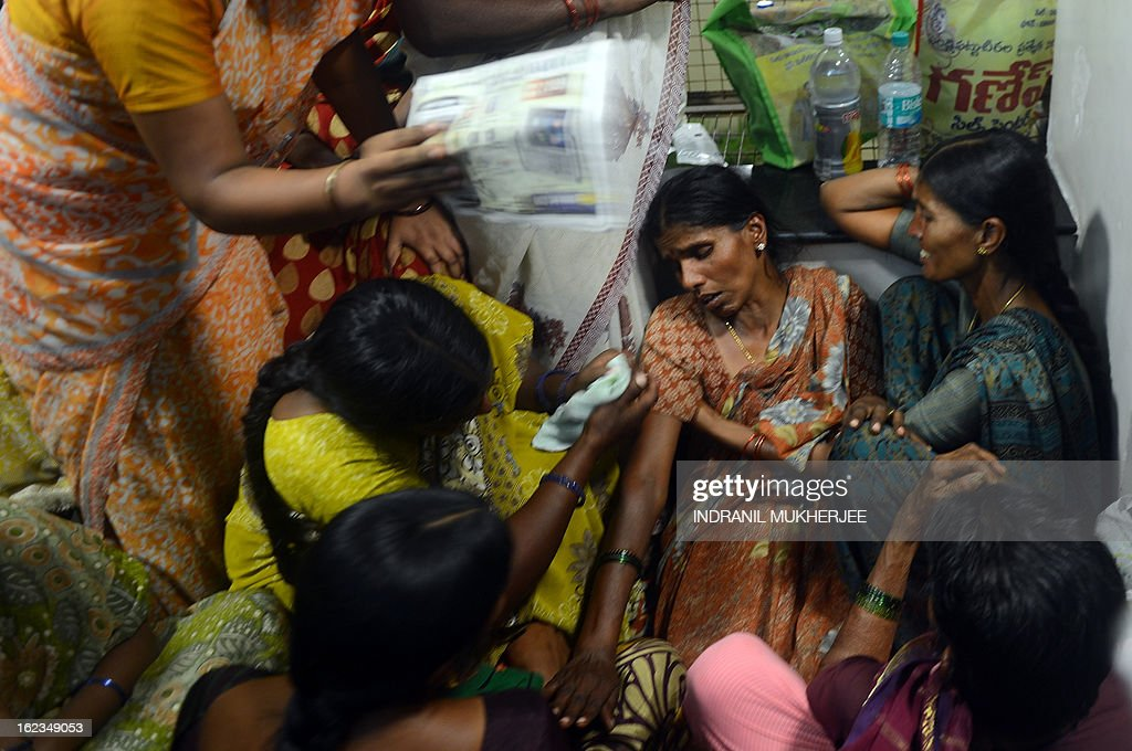 Friends and family members sit around the grieving relative (3R) of a bomb blast victim at the Yashoda Hospital in Hyderabad on February 22, 2013. Indian police revealed Friday they had been warned of a possible attack by Islamist militants in a bustling shopping area of Hyderabad where twin bombings killed at least 14 people and wounded scores. AFP PHOTO/Indranil MUKHERJEE