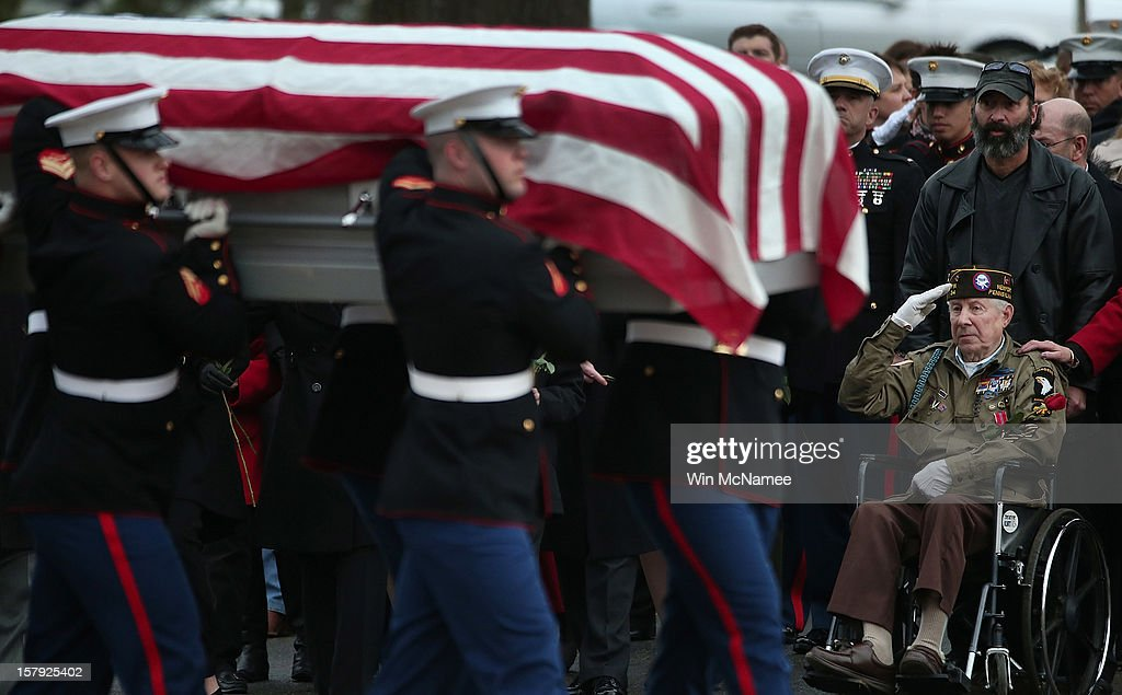 Friends and family of Marine Chief Warrant Officer 3 Gary Stouffer, watch as Stouffer's casket is carried by a Marine Corps honor guard during a burial service at Arlington National Cemetery December 7, 2012 in Arlington, Virginia. Stouffer, a combat veteran formerly deployed in both Iraq and Afghanistan, was one of four veterans killed when the float they were riding on was hit by a train during a Veterans Day parade in Midland, Texas on November 15.