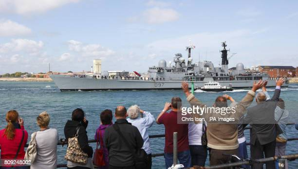 Friends and family of the crew wave to HMS Edinburgh as she leaves Portsmouth harbour bound for the South Atlantic for a seven month deployment She...