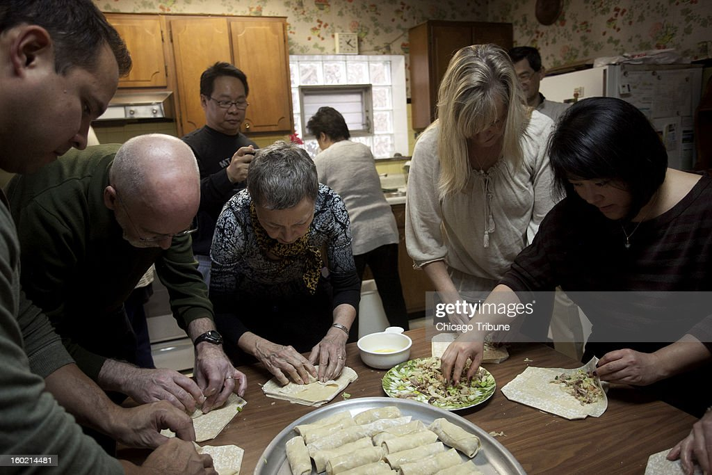 Friends and family roll egg rolls in Fanny Go's kitchen in Chicago, Illinois, December 8, 2012.