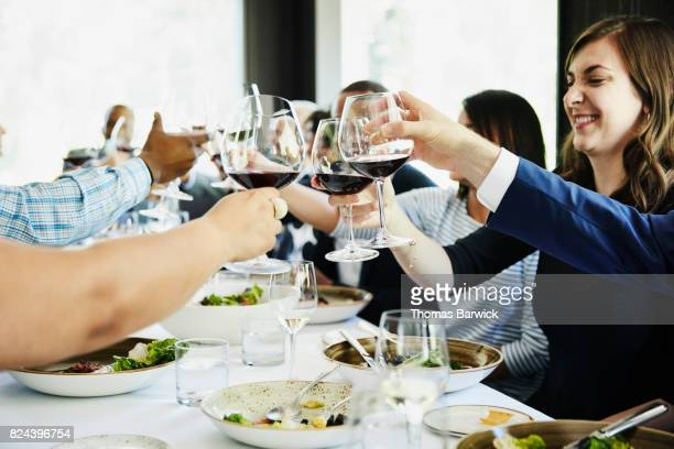 Friends and family toasting during celebration meal in restaurant