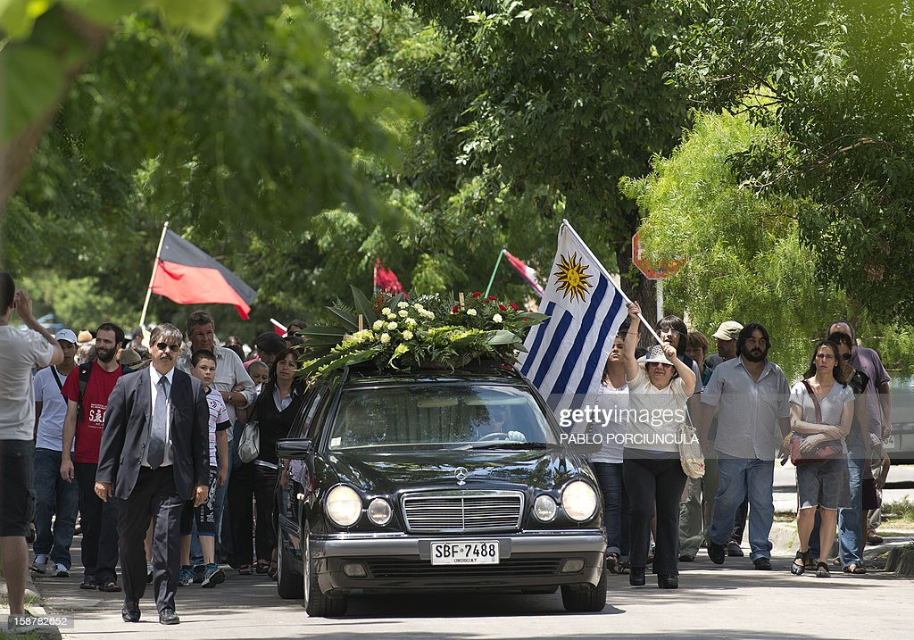 Friends and relatives accompany the funeral cortege carrying the remains of Uruguayan anarchist Alberto Mechoso, disappeared in Buenos Aires in 1976 during Argentina's military dictatorship, in Montevideo on December 28, 2012. The Uruguayan Government gave the remains of Mechoso to his relatives after being identified in Argentina. Mechoso was detained in September 26, 1976 and he was seen for the last time at the clandestine detention centre Automotoras Orletti on that year. AFP PHOTO/Pablo PORCIUNCULA