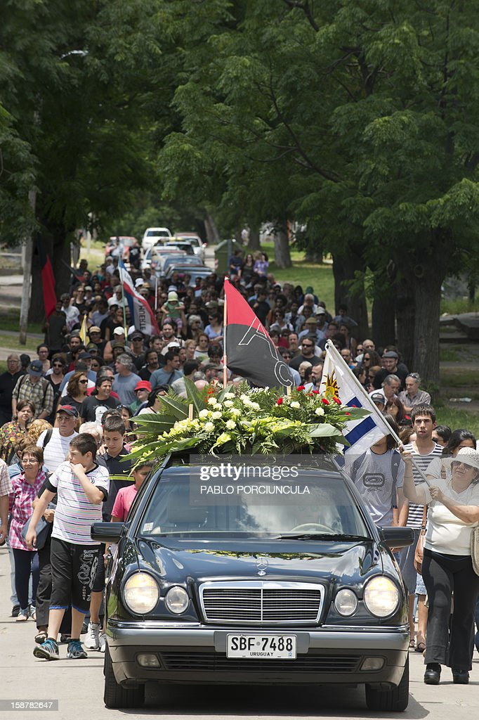 Friends and relatives accompany the funeral cortege of Uruguayan anarchist Alberto Mechoso, disappeared in Buenos Aires in 1976 during Argentina's military dictatorship, in Montevideo on December 28, 2012. The Uruguayan Government gave the remains of Mechoso to his relatives after being identified in Argentina. Mechoso was detained in September 26, 1976 and he was seen for the last time at the clandestine detention centre Automotoras Orletti on that year. AFP PHOTO/Pablo PORCIUNCULA