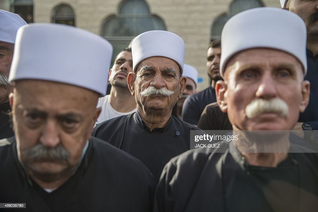 Friends and relatives look on near the coffin of Israeli police officer Zidan Saief a member of Israel's Druze minority during his funeral in his...
