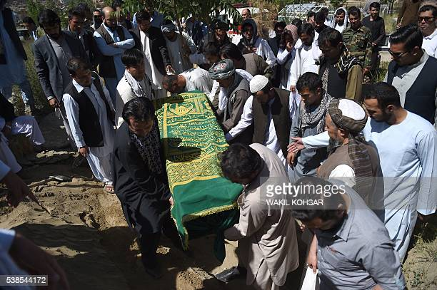 Friends and relatives lower the coffin of Afghan reporter Zabihullah Tamanna during his burial ceremony at the Shuhada cemetery in Kabul on June 7...