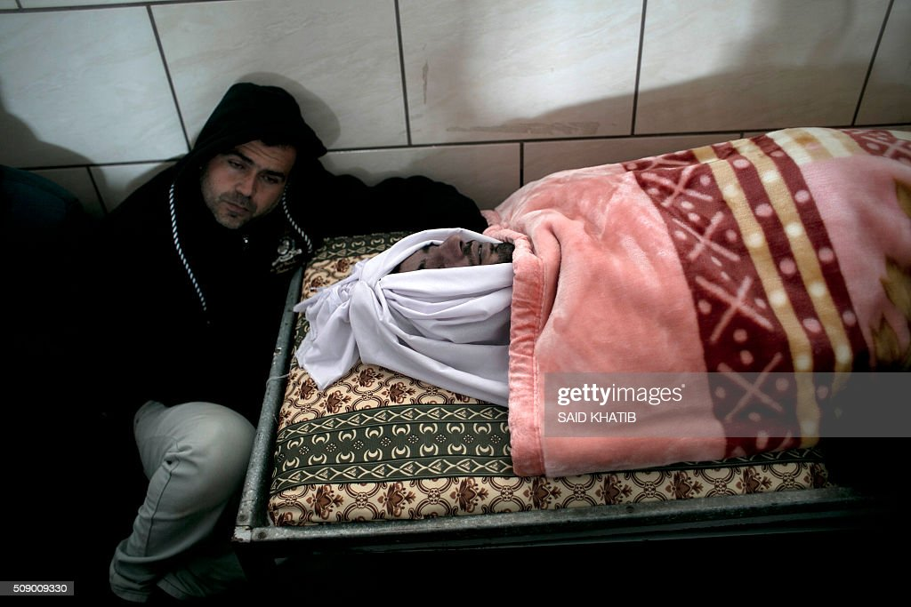 Friends and relatives mourn next to the body of Palestinian Mussa Jaber al-Maadi, who died after a tunnel collapsed, during his funeral on February 8, 2016, in Rafah in the southern Gaza Strip. Al-Maadi died when a tunnel he was trying to restore collapsed near Gaza's border with Egypt, Palestinian medical and security sources said. The death brings to 10 the number of Gazans killed in three separate tunnel collapses in two weeks. KHATIB