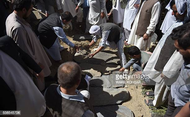 Friends and relatives of Afghan reporter Zabihullah Tamanna cover his grave with stones during his burial ceremony at the Shuhada cemetery in Kabul...