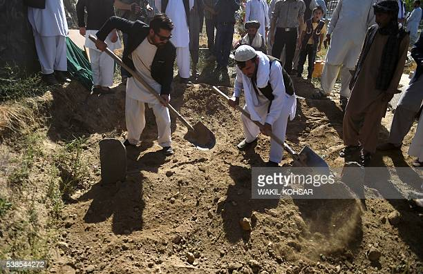 Friends and relatives of Afghan reporter Zabihullah Tamanna cover the grave with soil during his burial ceremony at the Shuhada cemetery in Kabul on...