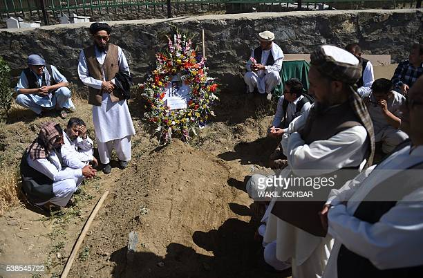 Friends and relatives of Afghan reporter Zabihullah Tamanna offer prayers during his burial ceremony at the Shuhada cemetery in Kabul on June 7 2016...