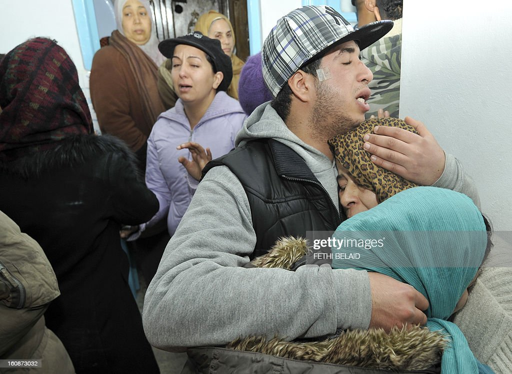 Friends and relatives of assassinated Tunisian opposition leader Chokri Belaid mourn on February 7, 2013 at his family home in the Tunisian capital's suburb of Jebel Jelloud. Police was deployed in force in Tunis amid fears the murder of Belaid could reignite nationwide violence, as the ruling Islamists broke ranks over how to defuse the crisis. Belaid's family said his funeral will take place on February 8 after the main weekly prayers.