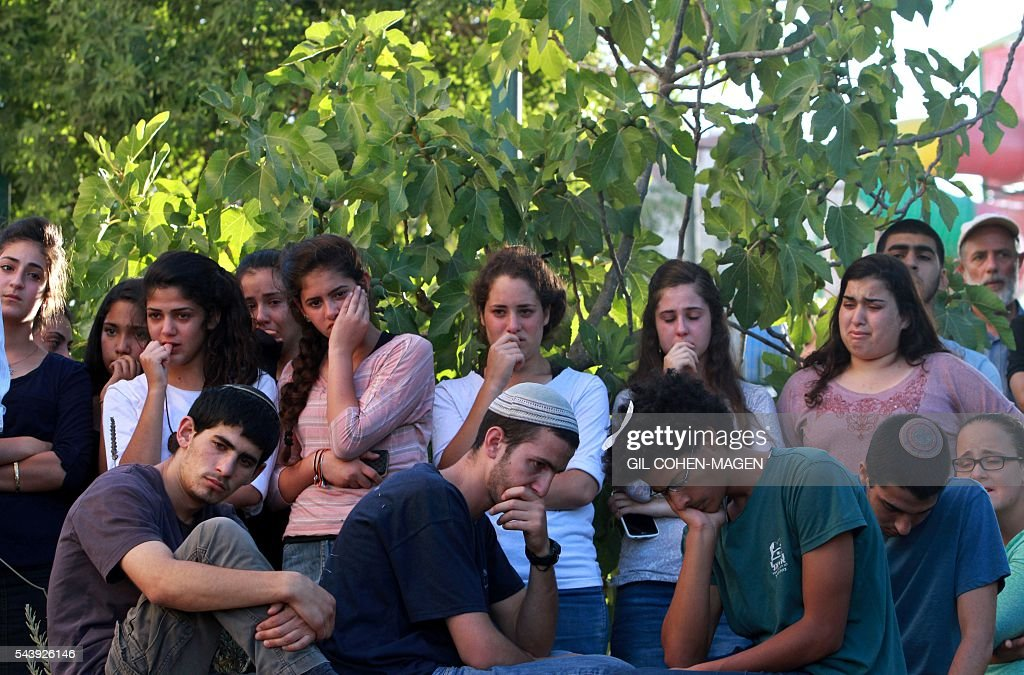 Friends and relatives of Israeli Hallel Yaffa Ariel, a 13-year-old girl who was fatally stabbed by a Palestinian attacker in her home, mourn during her funeral in the Kiryat Arba settlement outside the Israeli occupied West Bank city of Hebron on June 30, 2016. The Israeli army said that a young Palestinian killed Hallel in her bed after breaking into her home in the Kiryat Arba settlement outside the flashpoint city of Hebron. Security personnel rushed to the house and fired on the attacker, who wounded a guard before being shot dead, the army said. The girl was taken to hospital in Jerusalem in critical condition and died of her wounds. / AFP / GIL