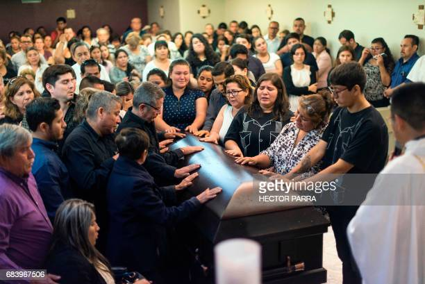 Friends and relatives of Mexican journalist Javier Valdez pray before his coffin in Culiacan Sinaloa State Mexico on May 16 2017 Valdez who worked...