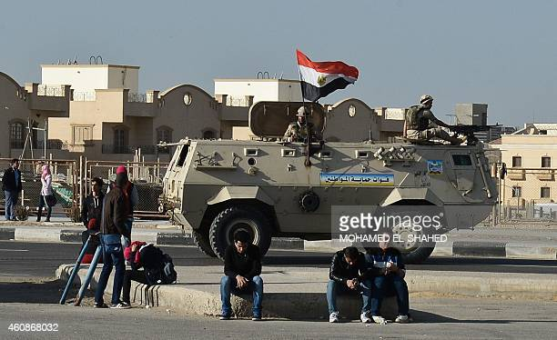 Friends and relatives of the twentythree Egyptian prodemocracy activists accused of holding an illegal protest last June sit next to an army vehicle...